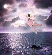 Little girl jumping into the night sky Stock Photos