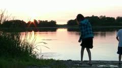 Kids Throwing Rocks into Lake Stock Footage