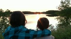 Kids Watch Sunset over Lake Together Stock Footage