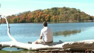 Man Sitting on Driftwood - Staring Out at Fall Foliage Stock Footage