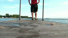 Man Walks to End of Dock and Sits Stock Footage