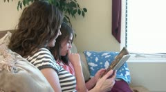 Mother & Daughter Read Together on Couch Stock Footage