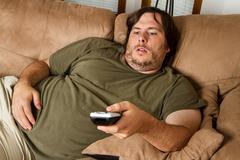 fat lazy guy on the couch - stock photo