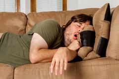 Man taking a quick nap on the couch Stock Photos