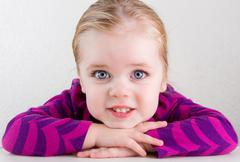 child resting her head on her hands smiling - stock photo