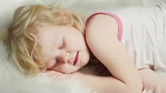 Little blond girl sleeping on white bed Stock Footage