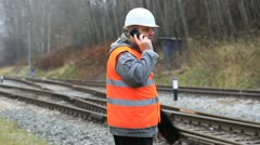 Employee on the railroad tracks with a cell phone Stock Footage