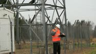 Stock Video Footage of Engineer at GSM tower with a cell phone