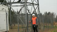 Stock Video Footage of Engineer at GSM tower with a cell phone and folder