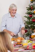 Stock Photo of Grandfather carving christmas turkey