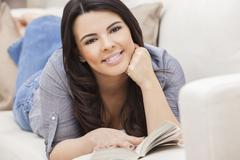 Stock Photo of happy hispanic woman reading paperback book at home