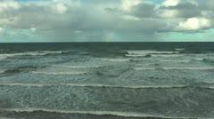 Rainbow on horizon over sea, gentle waves on beach Stock Footage