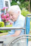 Vanhempi nainen pyörätuolin edessä talon Kuvituskuvat