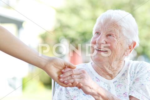 Stock photo of senior woman holding hands with caretaker