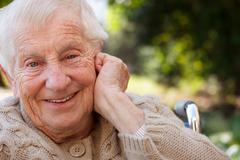 happy senior lady in wheelchair - stock photo