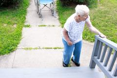 senior lady standing in front of staircase - stock photo