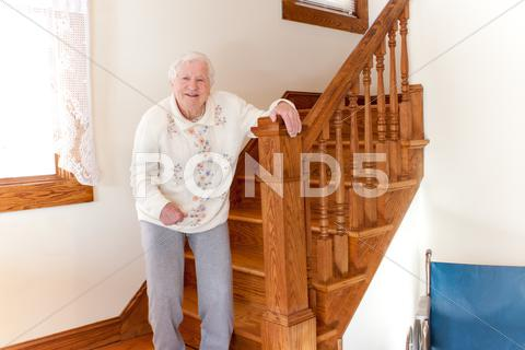 Stock photo of senior lady with staircase