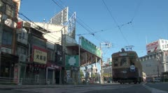 Low shot of streetcars in Hiroshima arriving at the tram stop Stock Footage