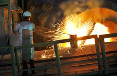 Molten hot steel pouring and worker Stock Photos