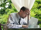 Businessman with laptop and documents reading bad news on terrace NTSC Stock Footage