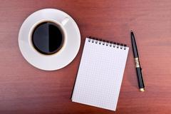 cup of coffee, notebook and pen - stock photo
