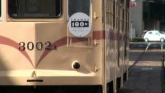 Closeup of a brown streetcar riding through the streets of Hiroshima, Japan Stock Footage