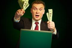 man with money in hands at the monitor - stock photo