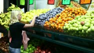 Girl chooses vegetables at the market. Stock Footage