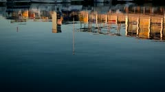 Calmed blue waters with boats and building reflection Stock Footage
