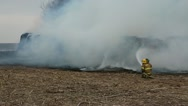 Stock Video Footage of firefighters spray round bales on fire in a field