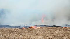 Wildfire moving through field engulfing a hay stack Stock Footage