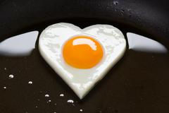 heart shaped egg in a frying pan - stock photo