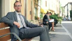 Successful happy businessman sitting on bench in the city HD Stock Footage