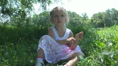 Child Playing with Grass in Park, Little Girl Sitting in the Grass Stock Footage