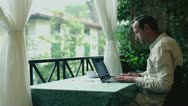 Young man with laptop computer relaxing on his balcony Stock Footage