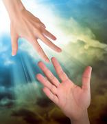 hand reaching for safety help in clouds - stock photo