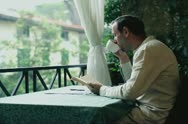 Young man with book relaxing on his balcony Stock Footage