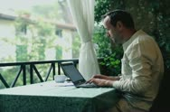 Young man with cellphone and laptop computer working on his balcony Stock Footage