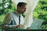 Businessman with cellphone and laptop computer working on his balcony Stock Footage