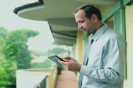 Businessman with tablet computer standing on balcony and working Stock Footage