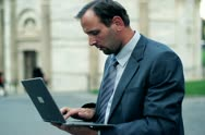 Portrait of smiling businessman with laptop computer in the city Stock Footage
