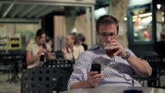 Happy young man using smartphone in bar, steadicam shot HD Stock Footage