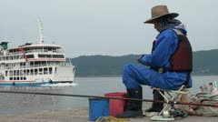 Japanese man fishing while ferry boat passes Stock Footage