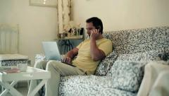 Young man sitting on sofa and teleworking from home Stock Footage