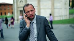 Business man in tourist city talking on his cell phone Stock Footage