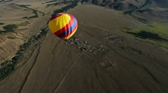 Hot Air Balloon flying across the sky in mountain landscape. Stock Footage