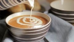 Swirling cream onto tomato soup Stock Footage
