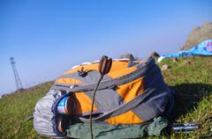 Knapsack at the top of the mountain with a flower - stock photo
