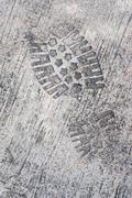 grunge textured concrete sidewalk shoe foot print - stock photo