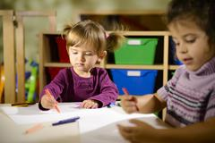 children and fun, two preschoolers drawing in kindergarten - stock photo